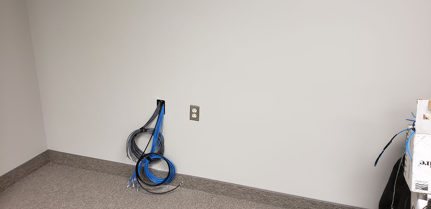blue and gray wires being passed through drywall